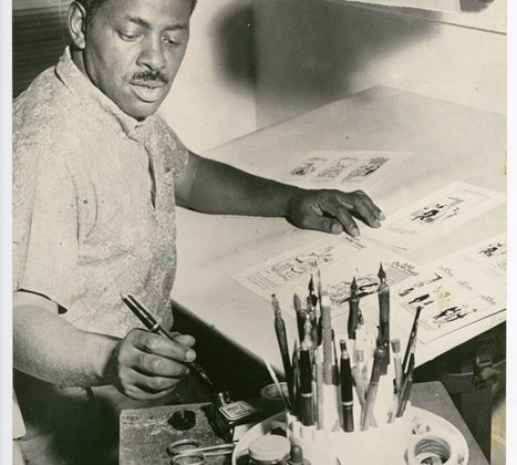 Morrie Turner at drafting table drawing characters